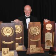 CU Skiing Coach Richard Rokos, standing with his NCAA Championship trophies