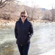 Elizabeth Koebele stands in her winter coat with the Arkansas River in the background.