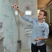 Computer Engineering Professor Aaron Clauset writes on white board
