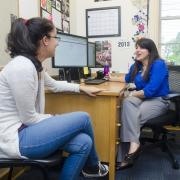 Academic advisor sits across desk from student