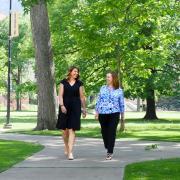 Staff members Alana Davis-Delaria and Eryn Elder walk on campus
