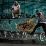 Boys skateboarding by a graffiti wall