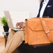 Man in suit types on laptop, with leather briefcase next to him