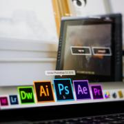 Person scrolls through Mac toolbar to open Adobe Photoshop