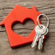Stock image of keys on a. keychain shaped like a house with a heart inside of it