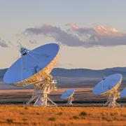Stock image of large satellite dishes in an open field