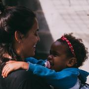 Babysitter holds smiling baby