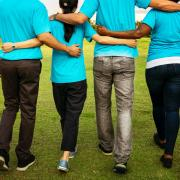Group of people walk with arms around each other