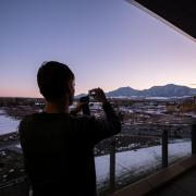 A visitor to the Aerospace Building takes a photo of the view during sunset