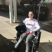 Aine Williams in wheelchair sporting a CU Lacrosse T-shirt