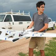 CU Boulder researcher holds drone with storm moving in