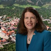 Ann Schmeising portrait with an aerial view of the cu boulder campus in the background