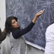 A faculty member demonstrates an applied mathematics lesson using a chalkboard.