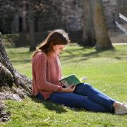 Student studying on lawn, leaned against a tree