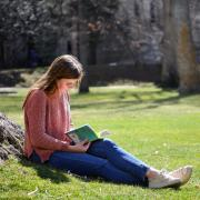 Student sitting against tree reading