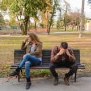 woman and man arguing while sitting on bench outside
