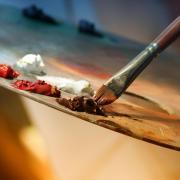 Artist dips brush in paint