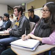 Students listen to lecture in a large classroom