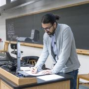 A faculty member, standing near a table and projector, appears to be teaching.