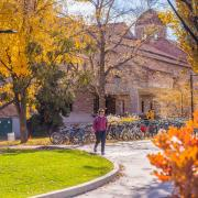 Student walks on campus with fall colors