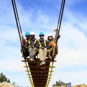 CU Boulder engineering students sit on suspension bridge