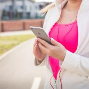 Woman checks smartphone app before going on a run