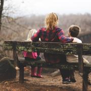 Adult sits with two kids on a park bench
