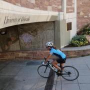 Person rides bike under bridge on CU campus
