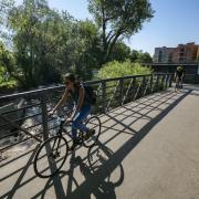 Woman bikes to work, with 28th Street apartments in background