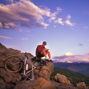Bicyclist writing and sitting on a mountain ridge