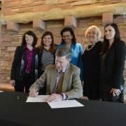 Gov. John Hickenlooper signs bill with people looking on.