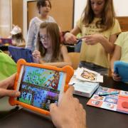 CU summer camp participants using a handheld device