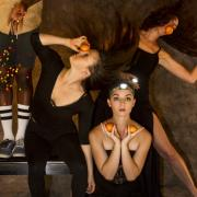 Dancers pose with oranges, headlamps and a skateboard