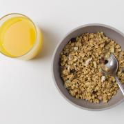Bowl of healthy cereal and glass of orange juice