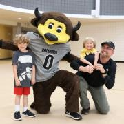 CU employee and children pose for a photo with Chip the Buffalo at the Rec Center