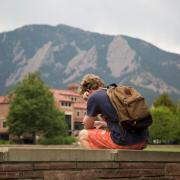 Student sitting alone on brick wall on campus