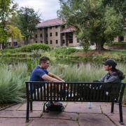 two students sit on a bench on campus, talking