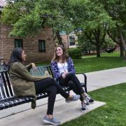 Two students sit on a bench talking