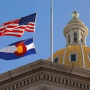 Denver capitol building with American flag and Colorado state flag