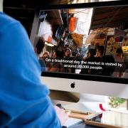 Man watches video with captions on iMac computer