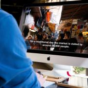 Man watching video with captions on iMac