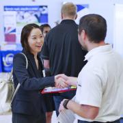 Student shakes hands with someone at a career fair in the UMC Ballroom