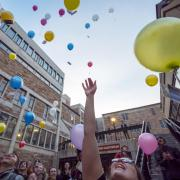 Students release biodegradable balloons as part of a course