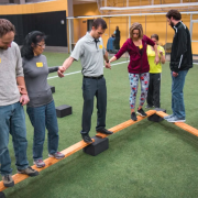 A group participates in an indoor challenge experience.