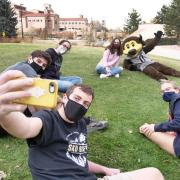 Students gather for a selfie with Chip the buffalo mascot outside