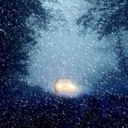 Car driving through snow storm