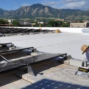 Brandon Bell, a technician from Lighthouse Solar, installs solar panels on the roof of the building which houses the University of Colorado Center for Innovation and Creativity in Boulder.