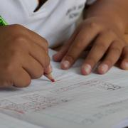 A child's hands as he or she does homework
