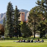 A class takes place outdoors on a grassy lawn.
