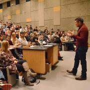 Carl Quintanilla speaks to students in large lecture hall